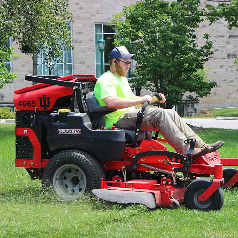 Indiana University maintenance worker cuts grass in front of a campus building.