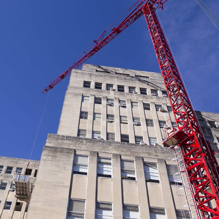 A crane lifts a piece of the building into place during renovations on Ballatine Hall.