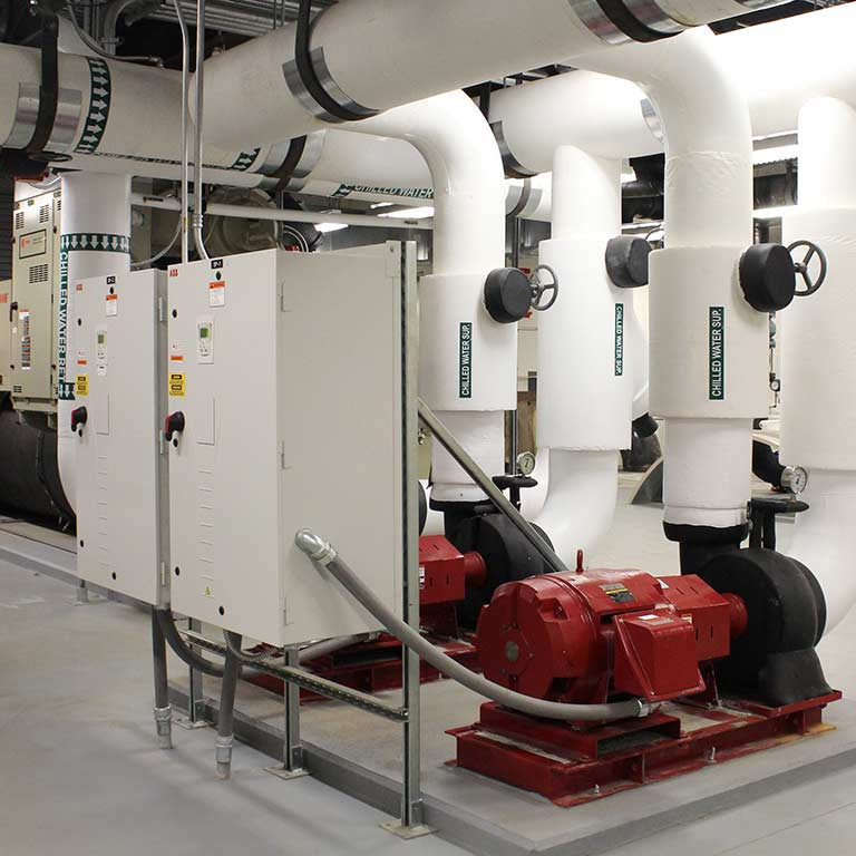 A utility room in a campus building with various water pipes and machinery
