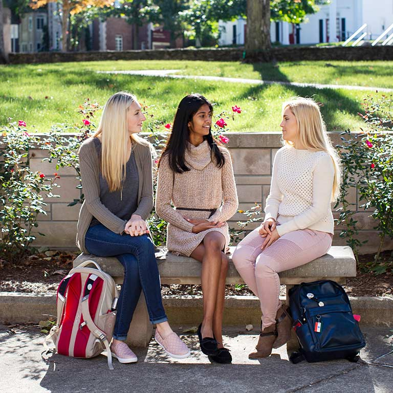 Three female students sit on a bench in front of rose bushes on the IU Bloomington campus.
