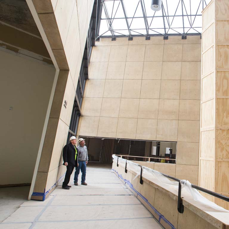 Two workers look at the ceiling of the Sidney and Lois Eskenazi Museum of Art.