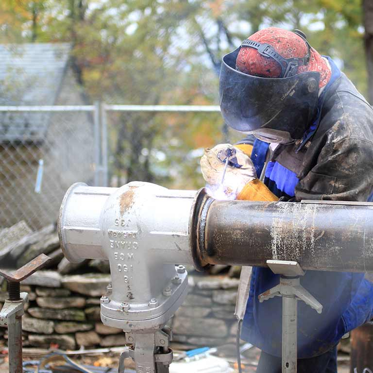 A worker repairs a metal pipe with a welding gun.
